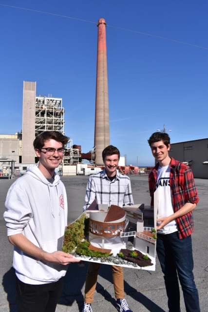 3 smiling high school students hold up the award-winning model they built of their original design proposal at the Potrero Point power plant.